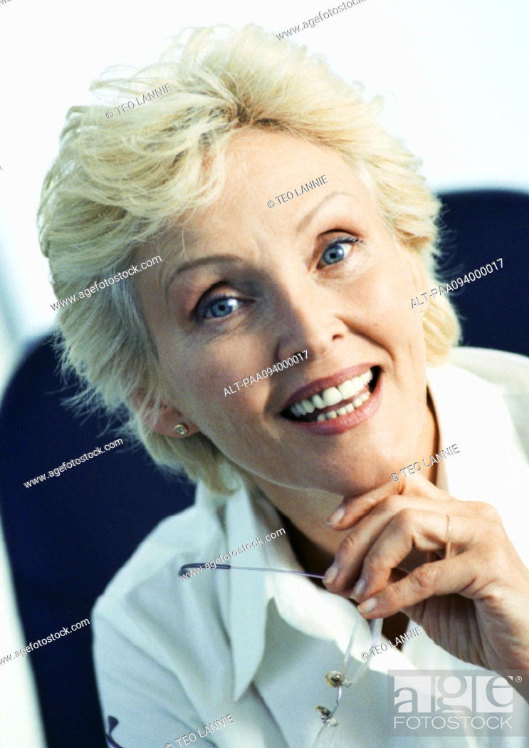 Stock Photo: Businesswoman holding glasses, smiling at camera, portrait.