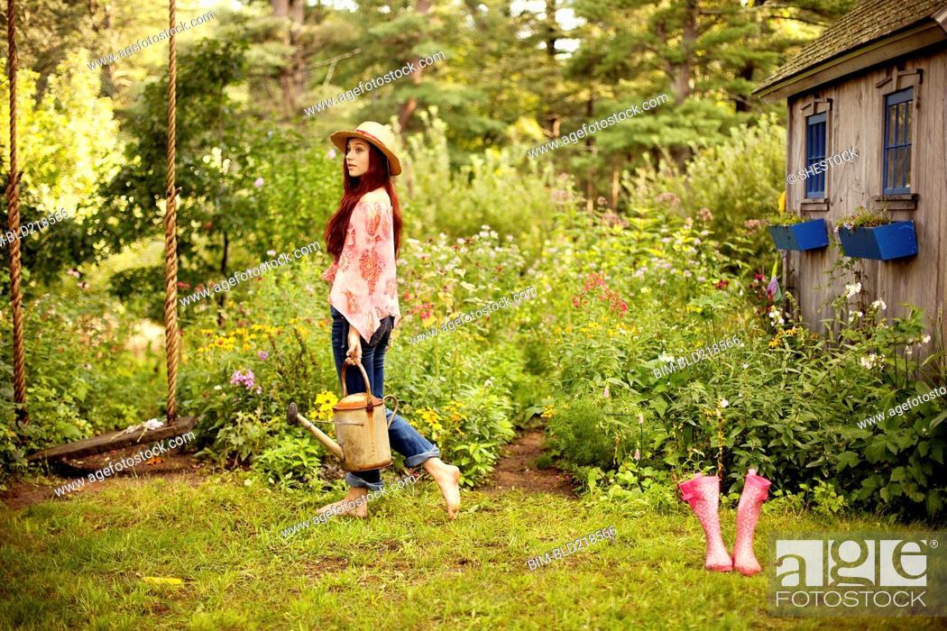 Stock Photo: Gardener picking flowers in garden.