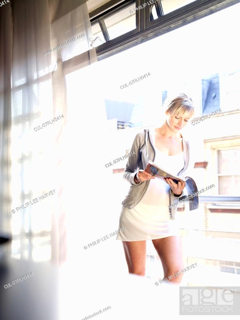 Stock Photo: Woman reading at window / balcony.