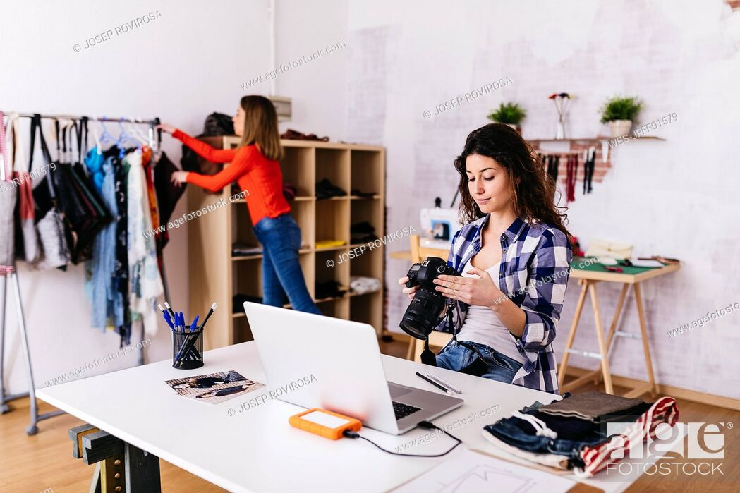 Stock Photo: Fashion designer with camera and laptop in studio.