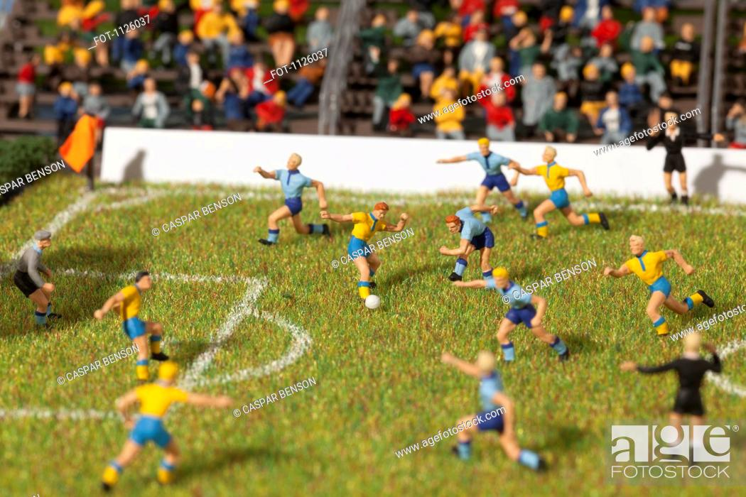 Stock Photo: Miniature figurines of two soccer teams playing a soccer match.