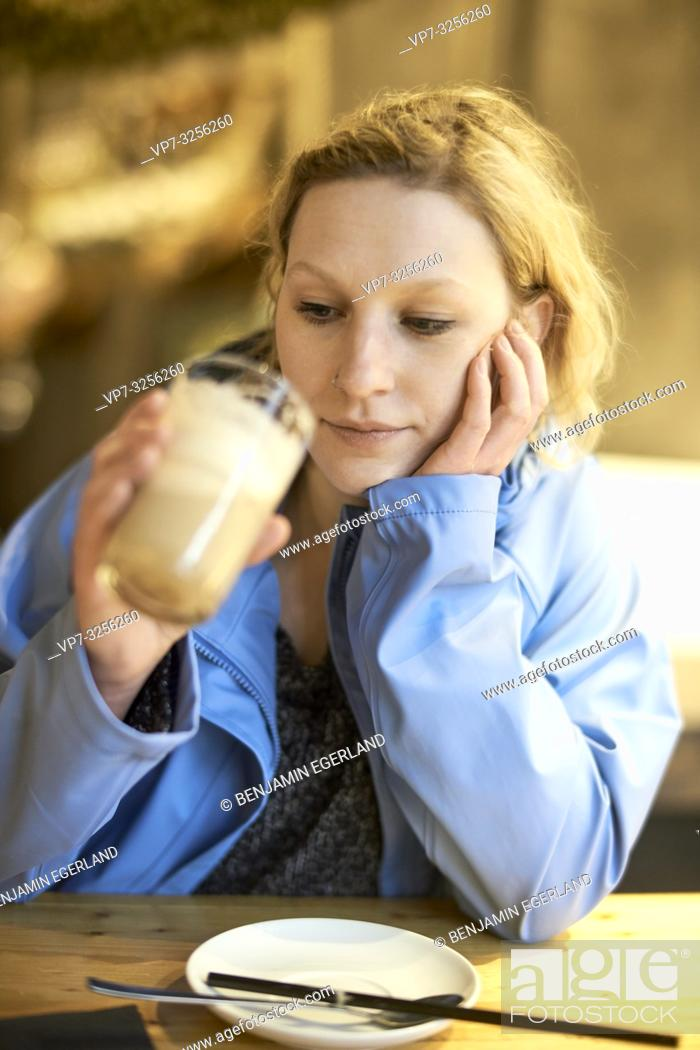 Stock Photo: Young woman in cafe, Munich, Germany.
