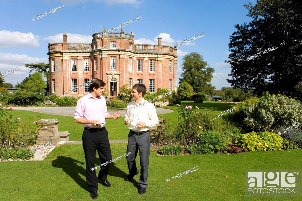 Stock Photo: Young man in conversation with friend in gardens of manor house.