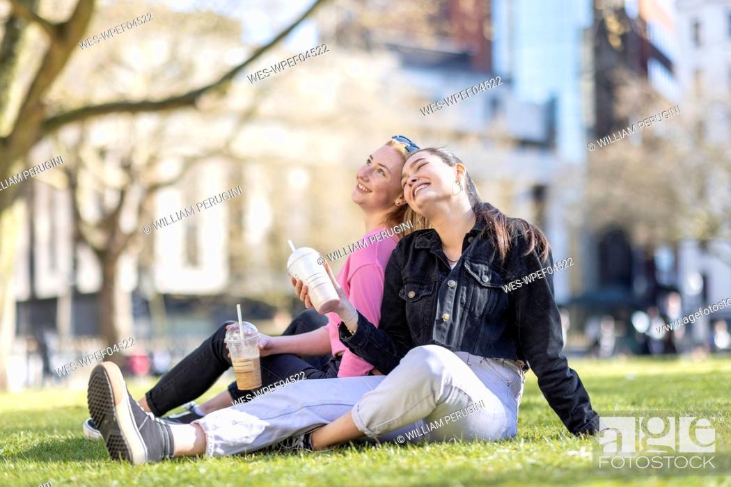Imagen: Cheerful female friends sitting at park.