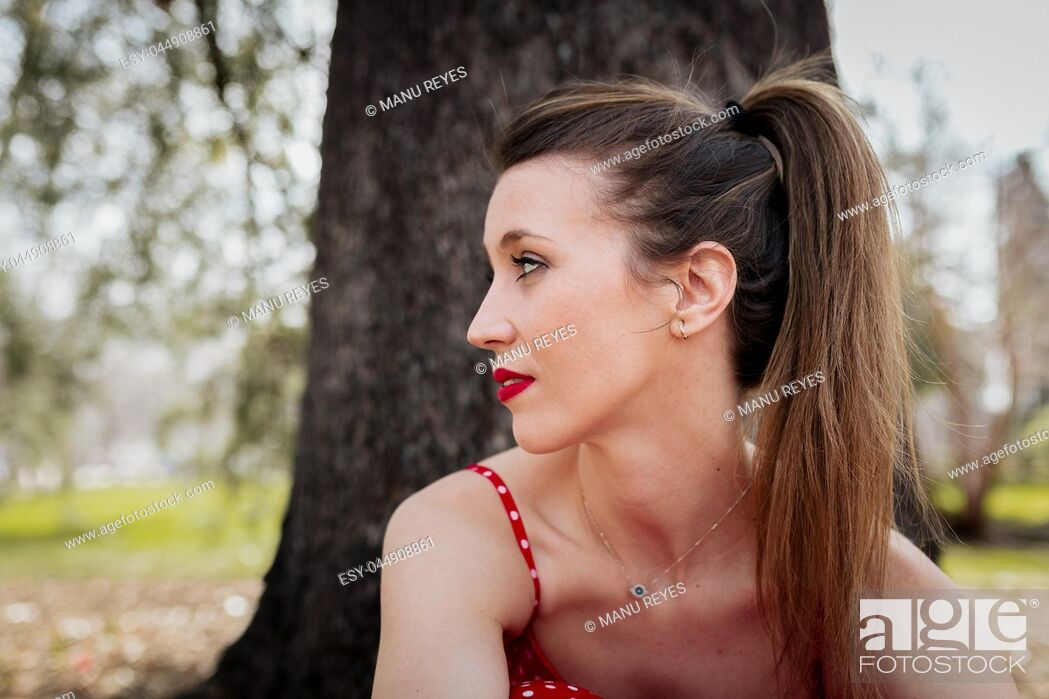 Stock Photo: Young serious blond woman with red long dress an a pigtail.