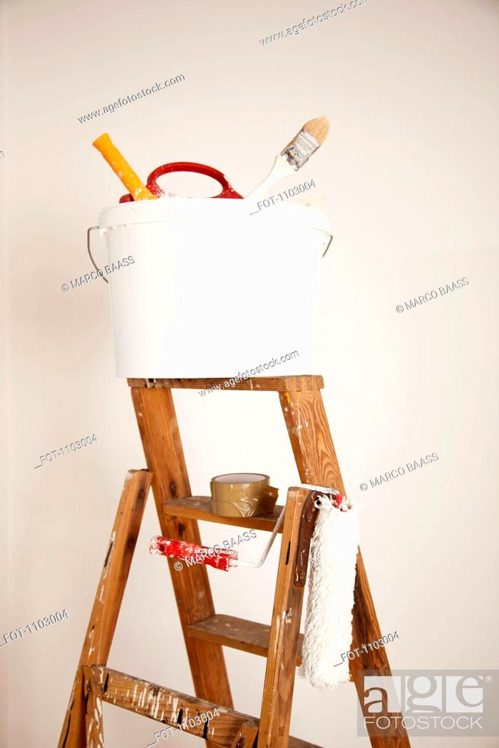 Stock Photo: A bucket of paint supplies and paint roller on a step ladder, still life.