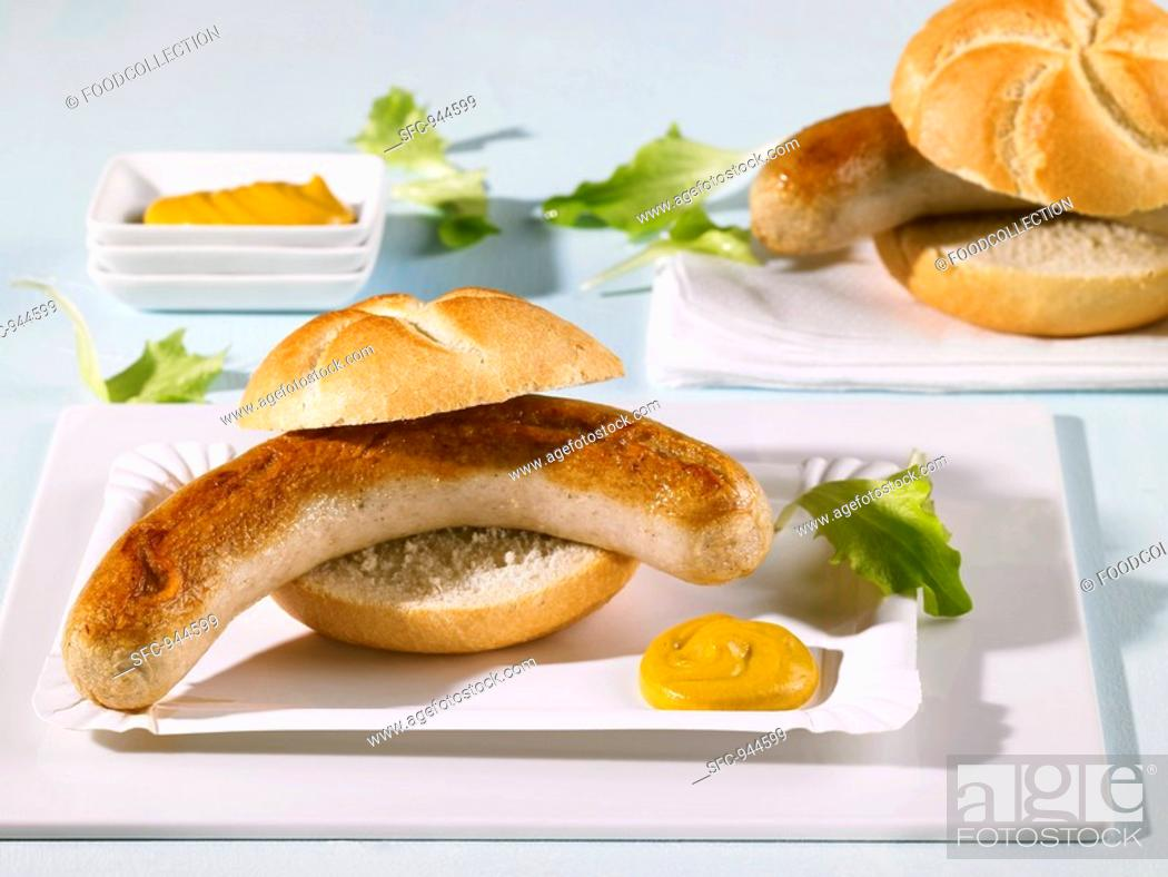 Stock Photo: Two bread rolls filled with sausages on paper plates.