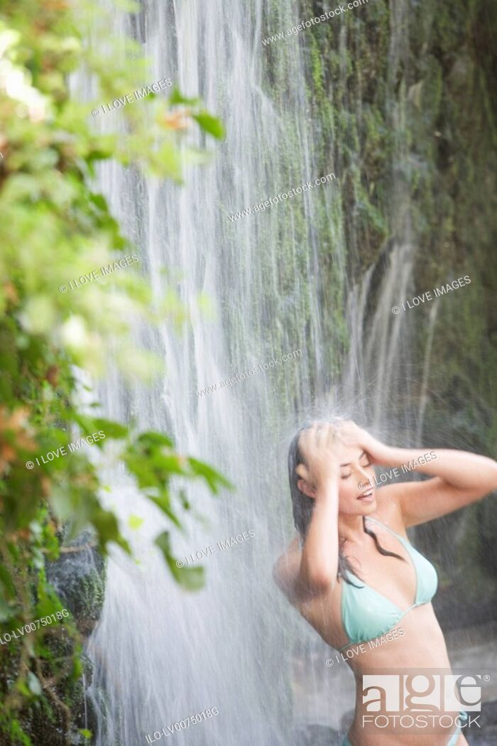 Stock Photo: A woman standing in a waterfall.
