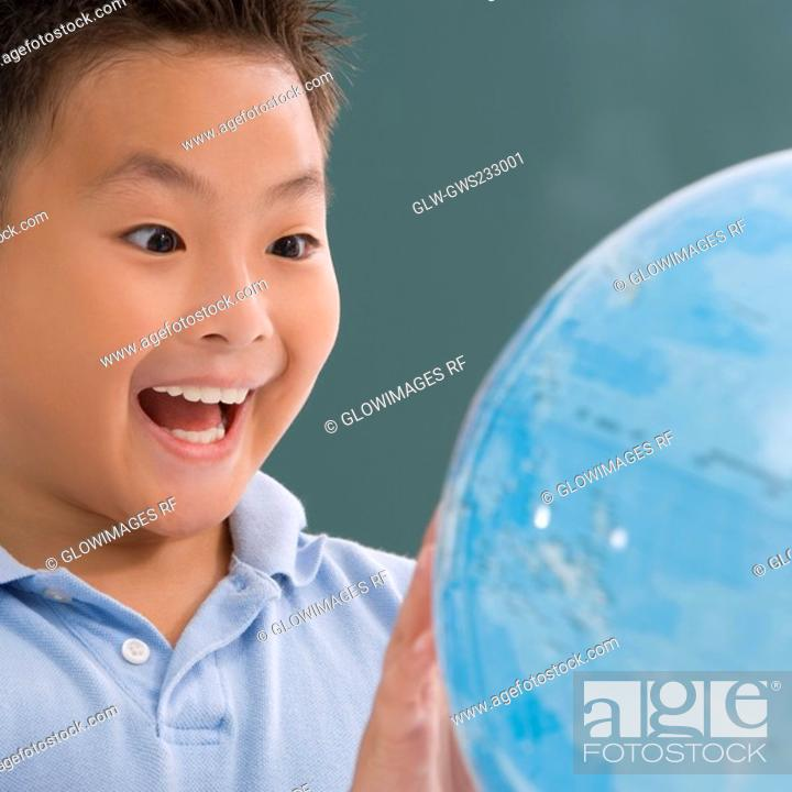Stock Photo: Close-up of a schoolboy looking at a globe and laughing.