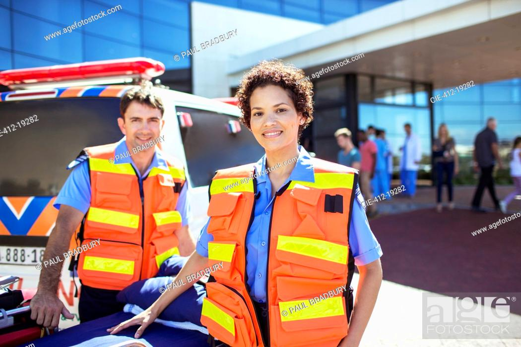 Stock Photo: Paramedics smiling by ambulance in hospital parking lot.