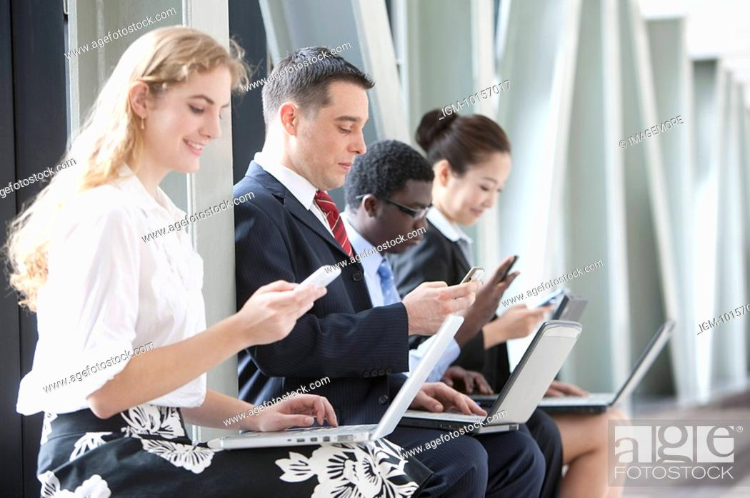 Stock Photo: Business people sitting in a row with laptop, each using mobile phones.