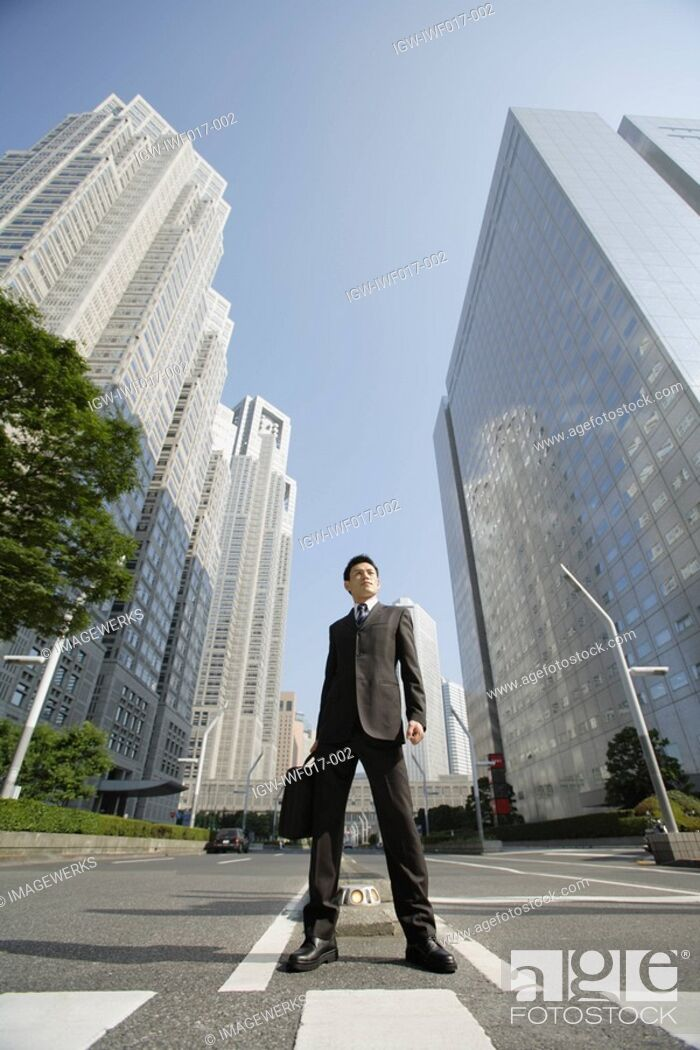 Stock Photo: Businessman amid office buildings.