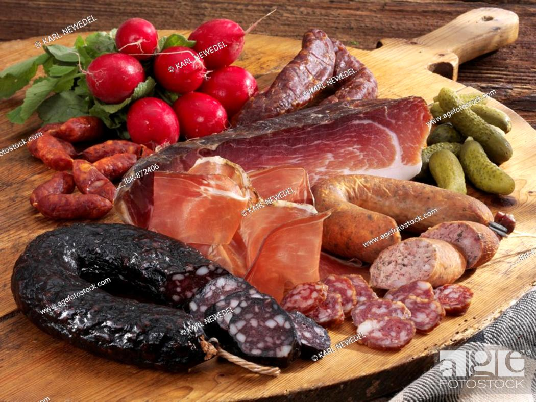 Stock Photo: Cold platter, wooden tray with Tyrolean ham, farmer's blood sausage, liver sausage, smoked kaminwurz, radishes and gherkins.