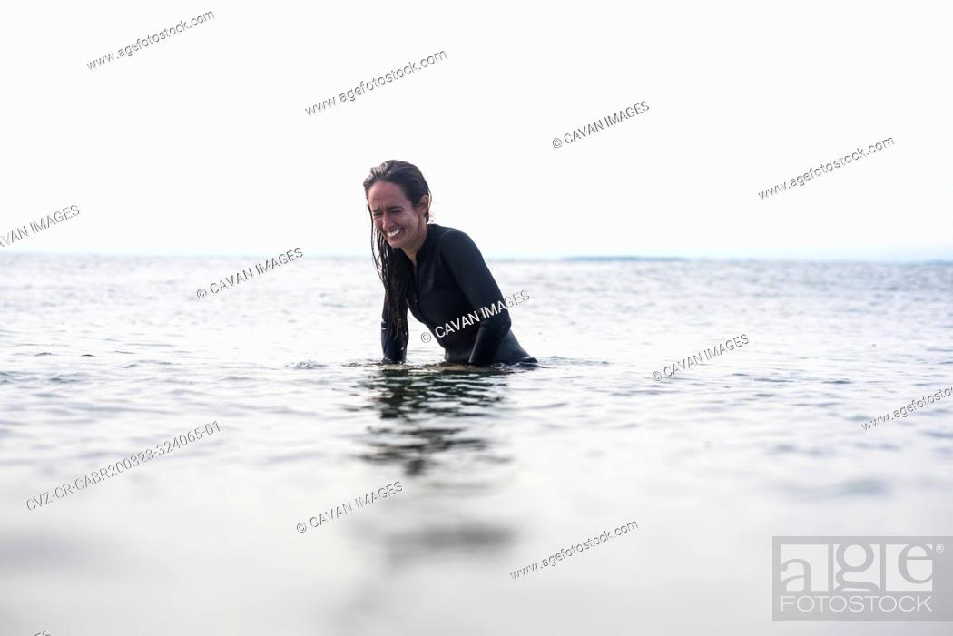 Stock Photo: Woman laughing in the ocean waiting for surf.