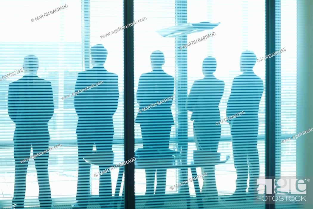 Stock Photo: Silhouette of business people in a row looking out office window.