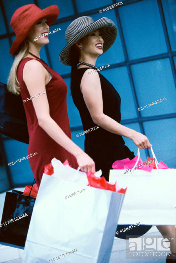 Stock Photo: Side profile of two young women carrying shopping bags.