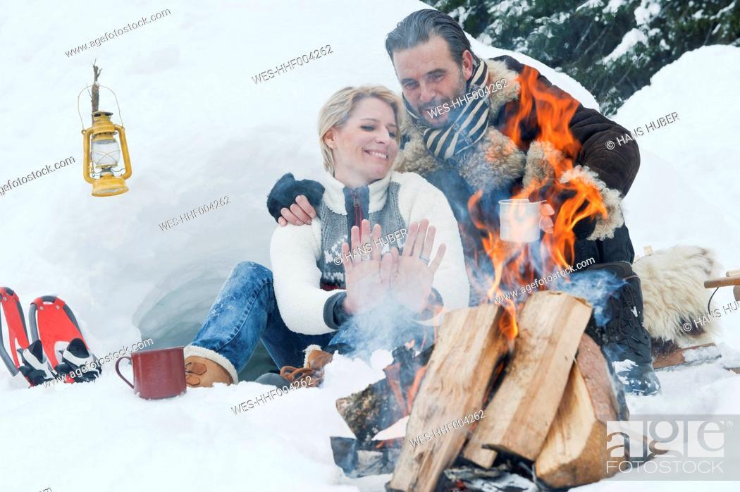Stock Photo: Austria, Salzburg County, Couple sitting near fireplace.