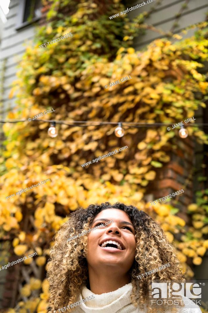 Stock Photo: Smiling woman looking up against autumn bush.