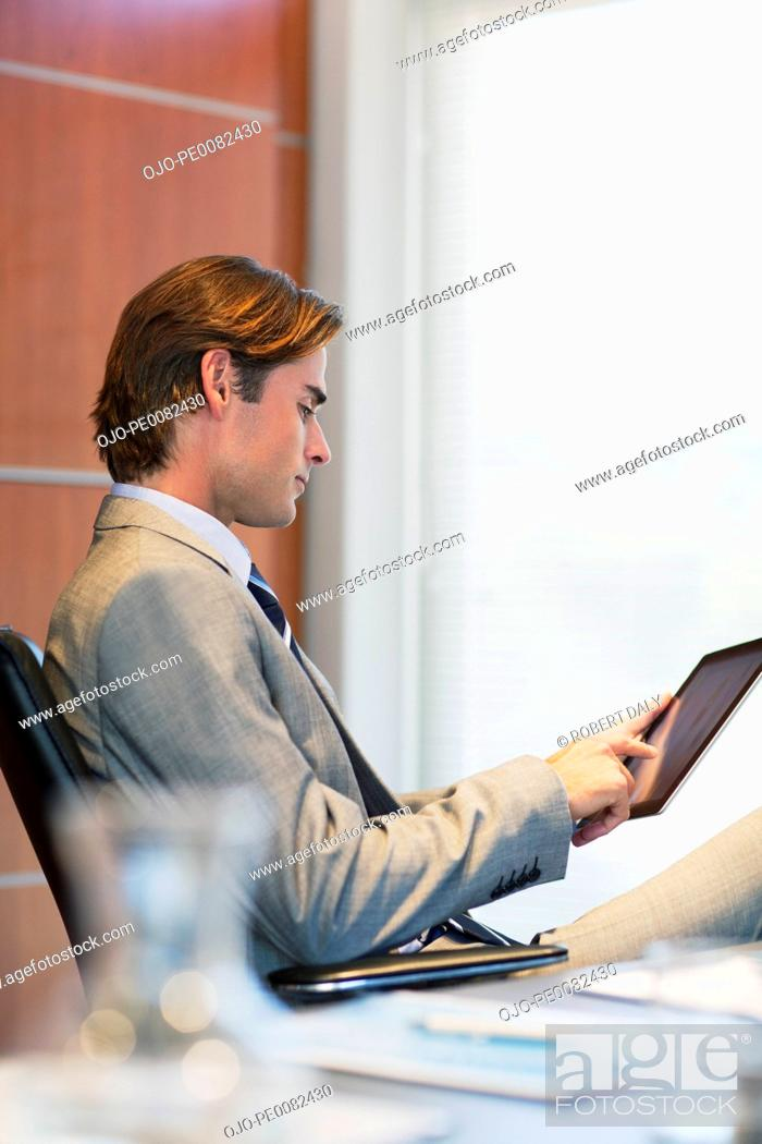 Stock Photo: Businessman using digital tablet in office.