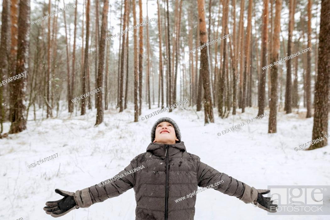 Stock Photo: Boy catching snowflakes in winter forest.