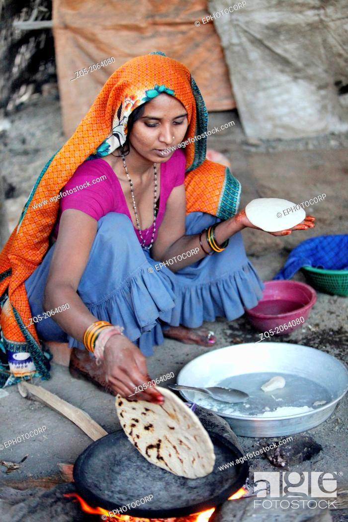 Stock Photo: Village woman making bhakaris or Indian bread, Jhabua, Madhya Pradesh, India.