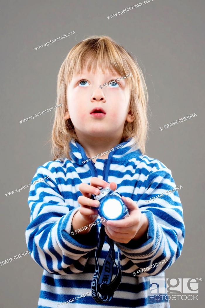 Stock Photo: boy with long blond hair playing with flashlight.