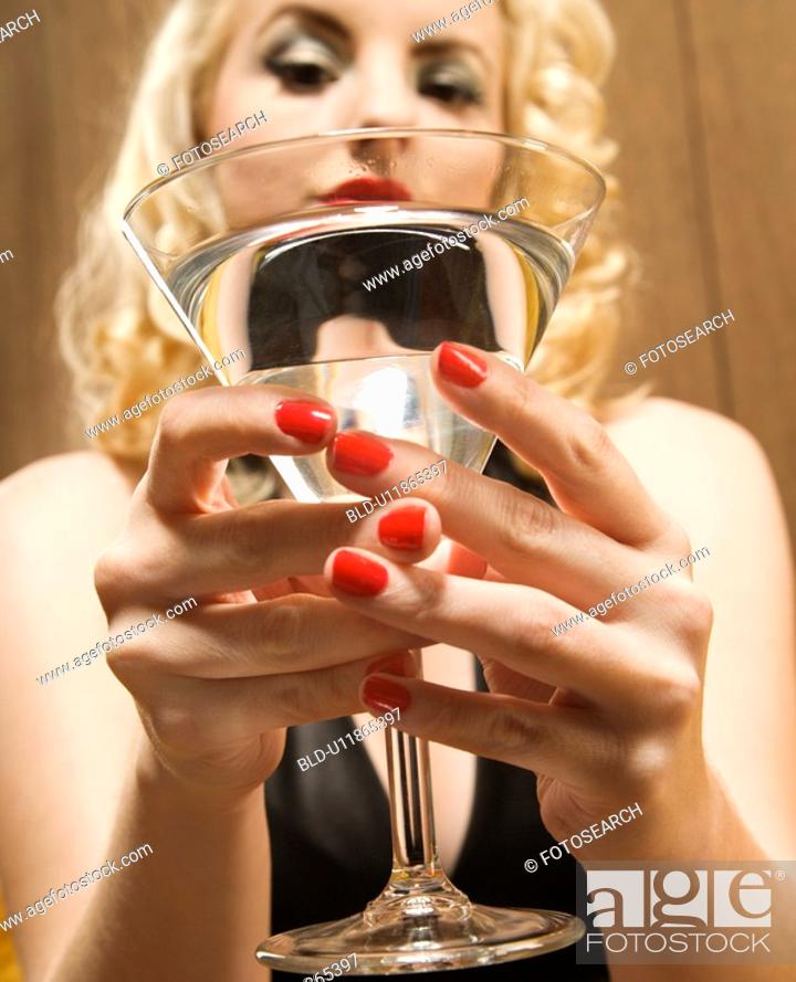 Stock Photo: Attractive woman holding a martini out to viewer.