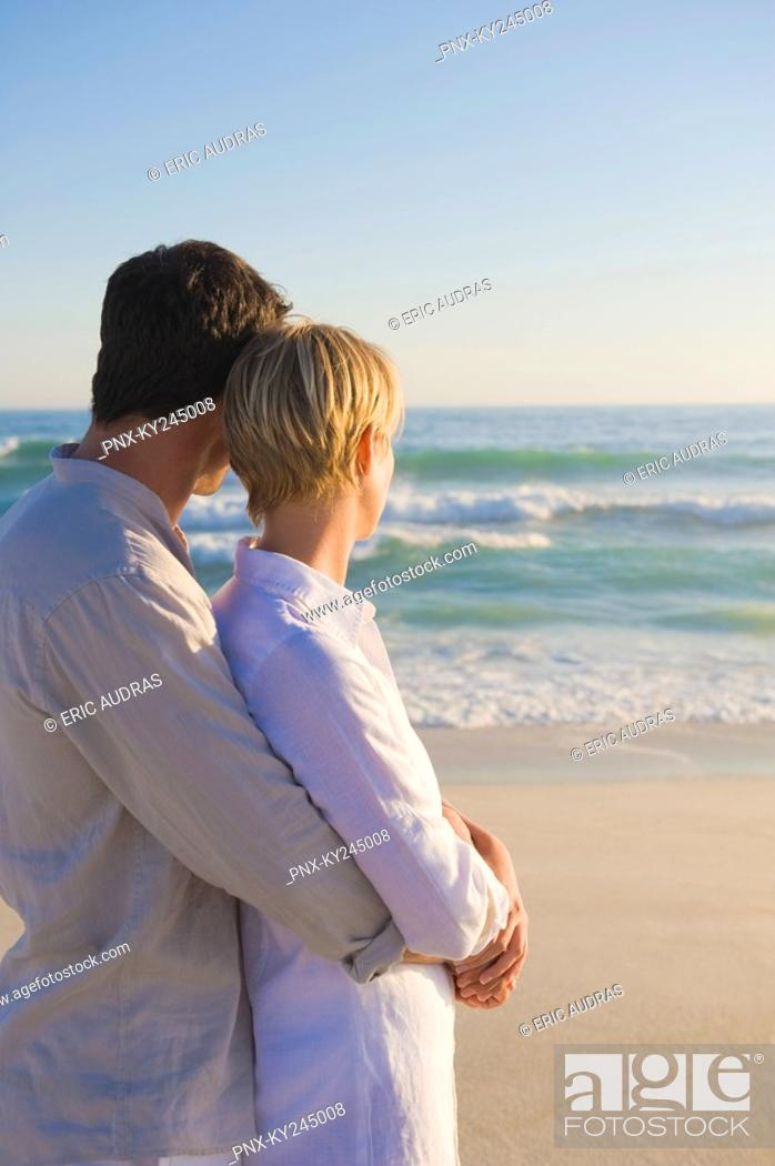 Stock Photo: Man embracing a woman from behind.