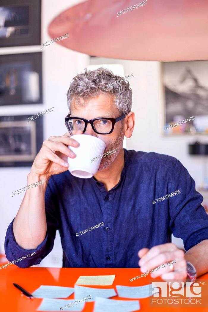 Stock Photo: Portrait of mature man at table with notepads drinking coffee.