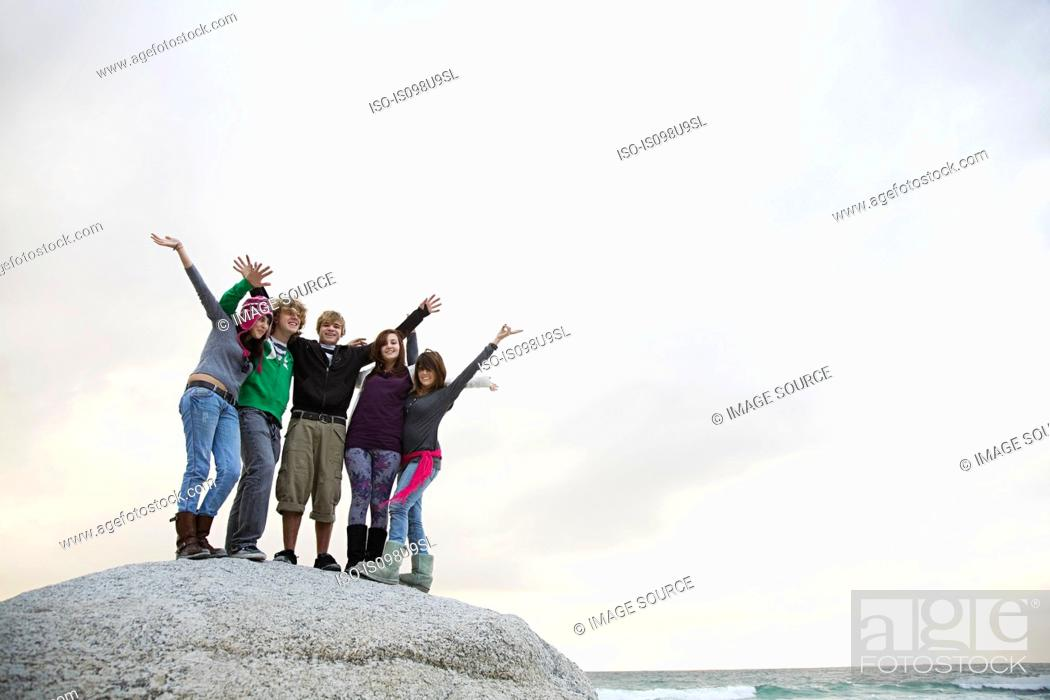 Stock Photo: Group of friends standing on boulder.