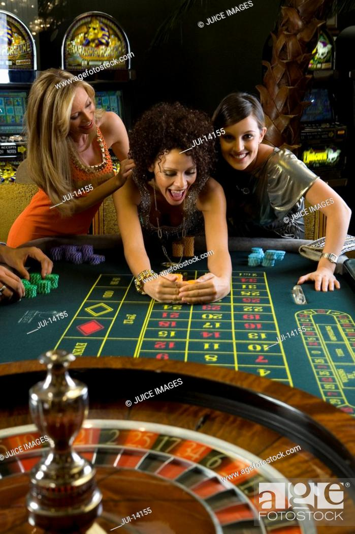 Stock Photo: Young woman collecting pile of gambling chips from roulette table, flanked by friends, smiling.