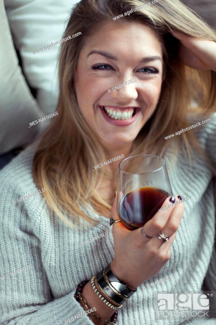 Stock Photo: Portrait of laughing blond woman with glass of coffee relaxing on couch at home.