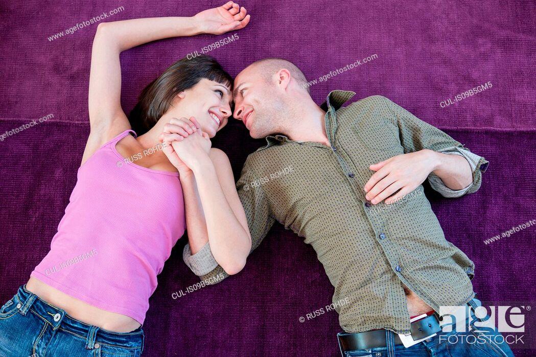 Stock Photo: Couple lying on carpet.