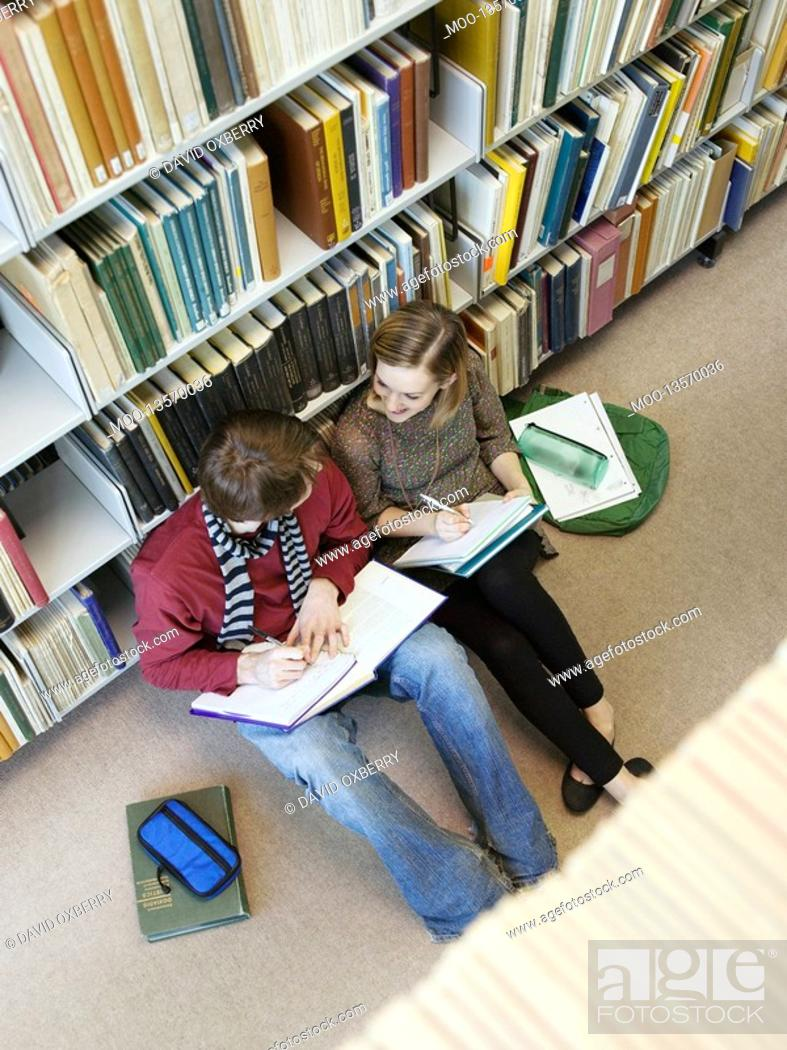 Stock Photo: Students sitting on floor doing homework in library.