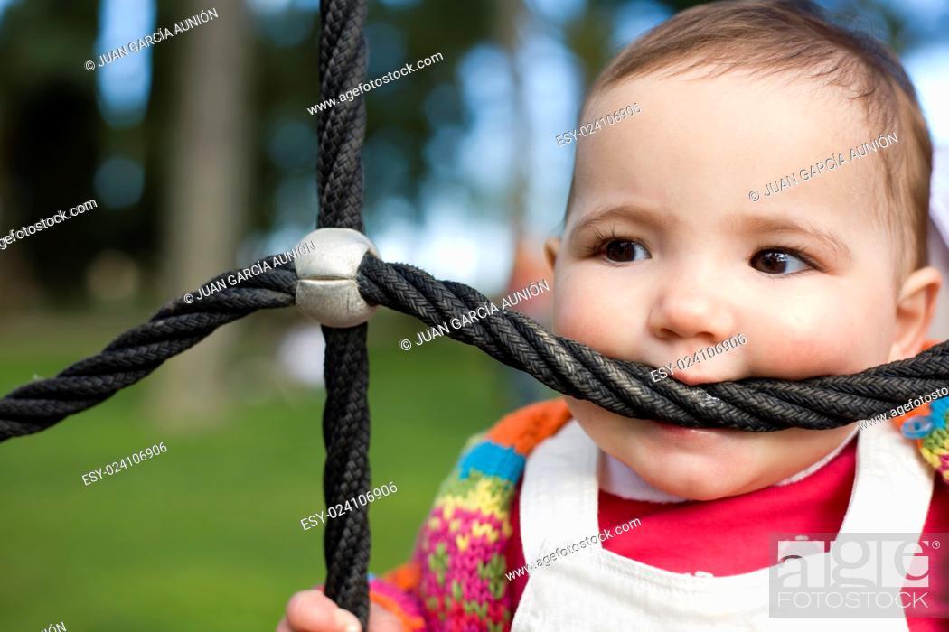 Photo de stock: Beautiful baby little girl bitting playground rope.