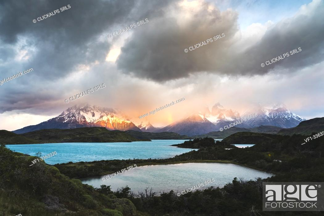 Stock Photo: Pehoé Lake and rainbow at dawn, with Cerro Paine Grande, Paine Horns and Cerro Paine covered in mist in the background. Torres del Paine National Park.