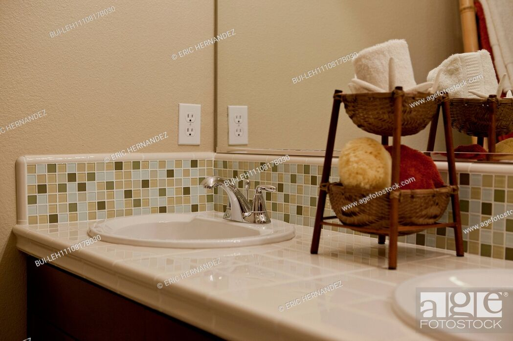 Imagen: Close-up of tiled counter and washbasin in the bathroom at home; California; USA.
