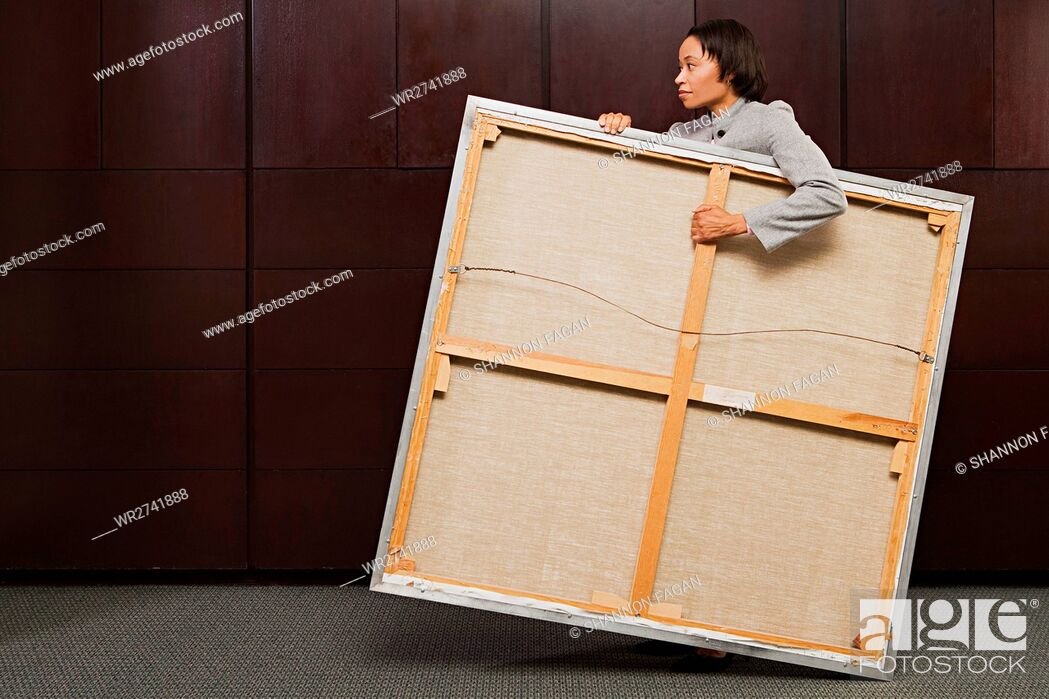 Stock Photo: Business woman carrying canvas.