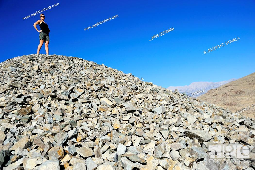 Stock Photo: Woman stands on tailing pile of old gold mine, Alabama Hills, California, USA.