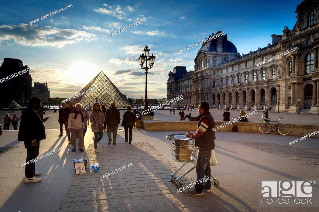 Stock Photo: Chestnut seller at Louvre Pyramid at sunset.