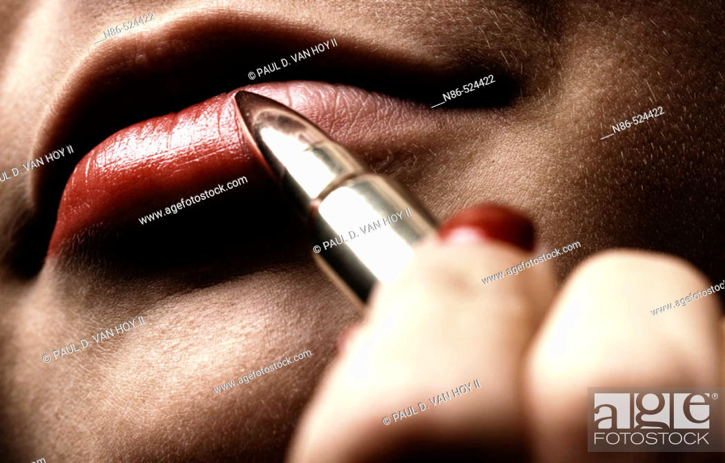 Stock Photo: Woman applying lipstick with bullet, conceptual.