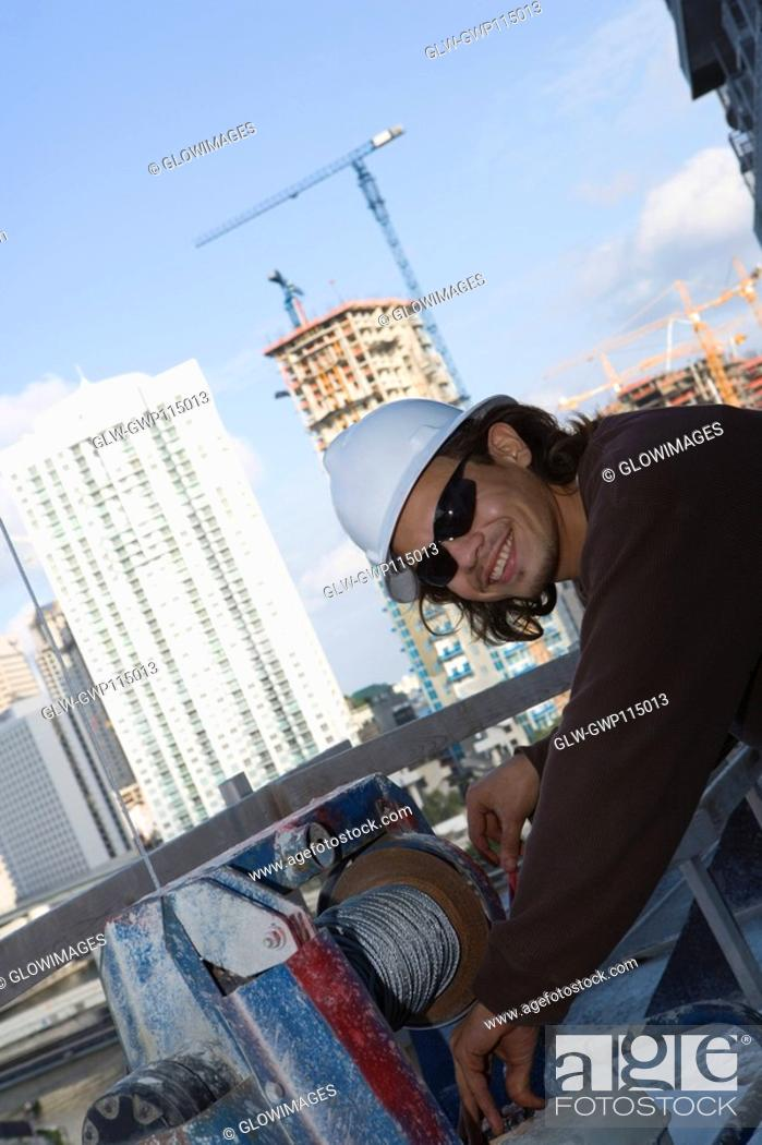 Stock Photo: Side profile of a male construction worker working at a construction site.
