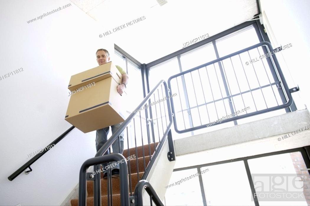 Stock Photo: Man carrying stacked boxes down staircase.