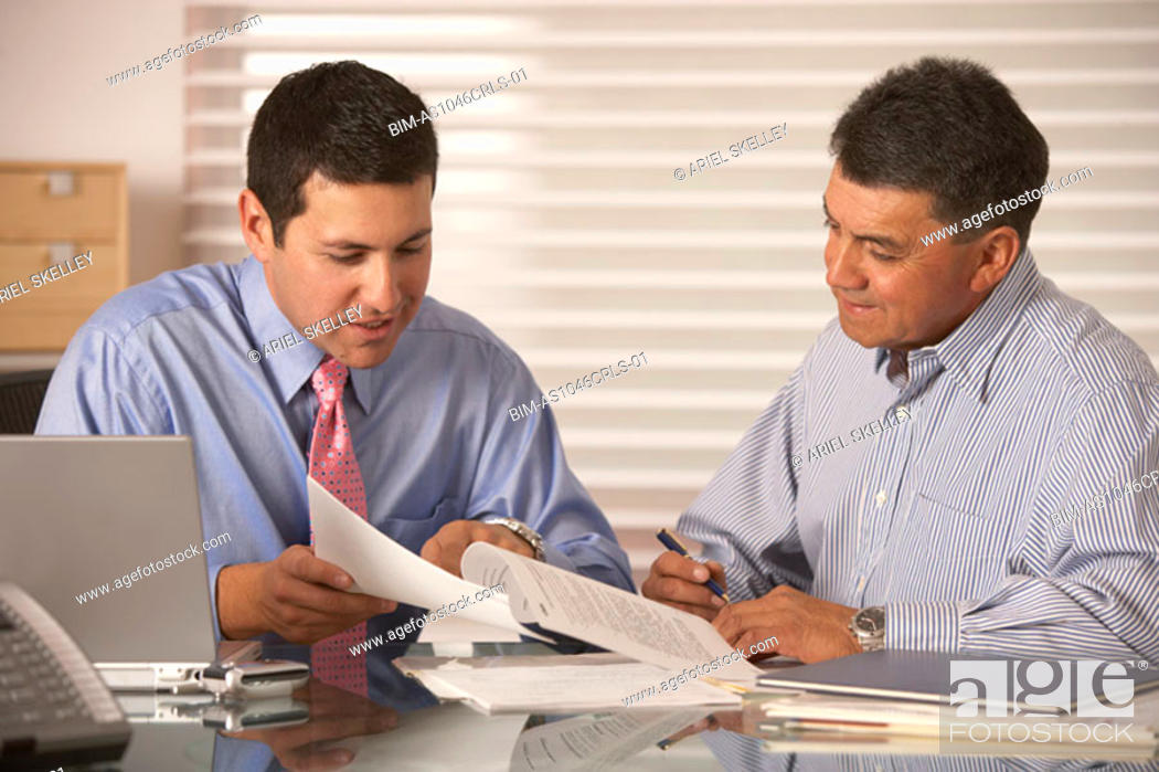 Stock Photo: Two businessmen reading papers at desk.