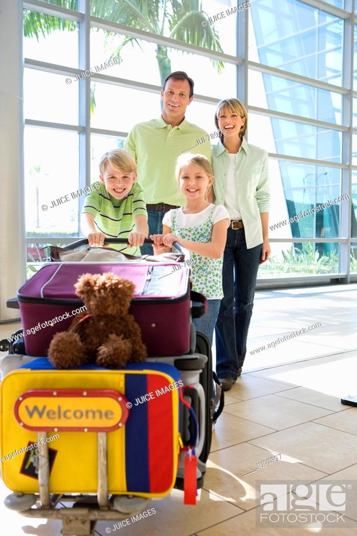 Stock Photo: Family standing beside luggage trolley in airport, smiling, front view, portrait, soft toy on suitcase.
