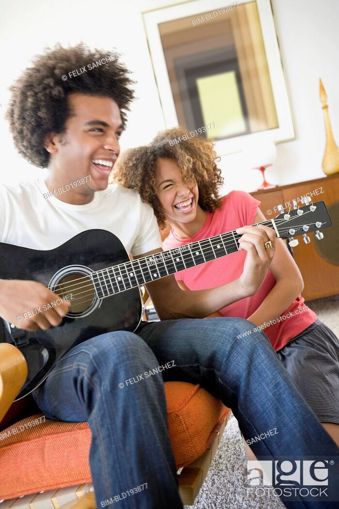 Imagen: Woman laughing while boyfriend plays guitar.