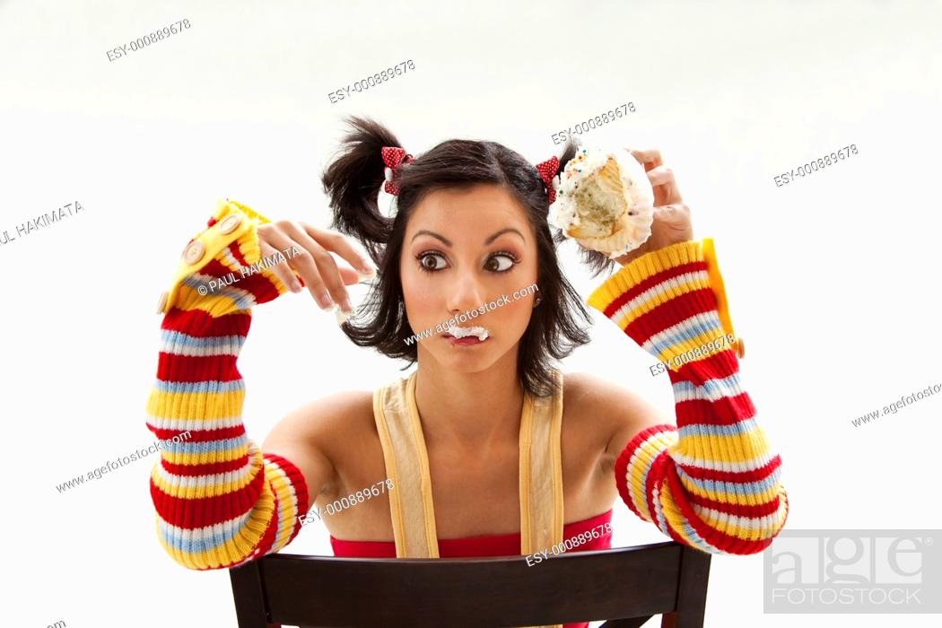 Stock Photo: Beautiful Latina girl eating a cupcake with her fingers looking cross eyed, isolated.
