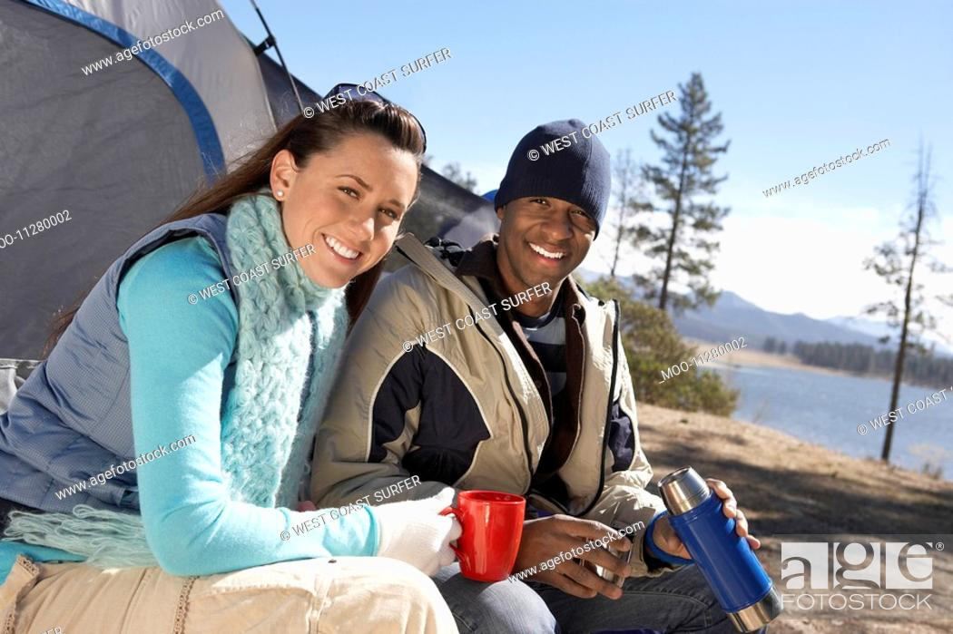 Stock Photo: Young Couple sitting at campsite drinking from thermos.