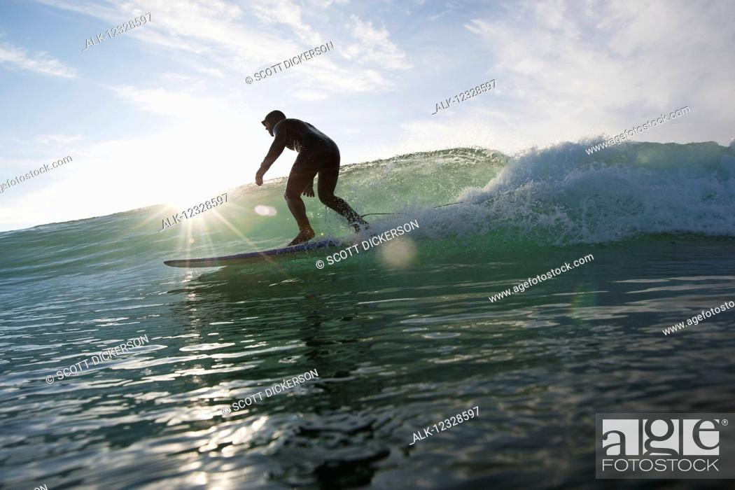 Stock Photo: Man surfing and backlit by the sunlight, South-central Alaska; Homer, Alaska, United States of America.
