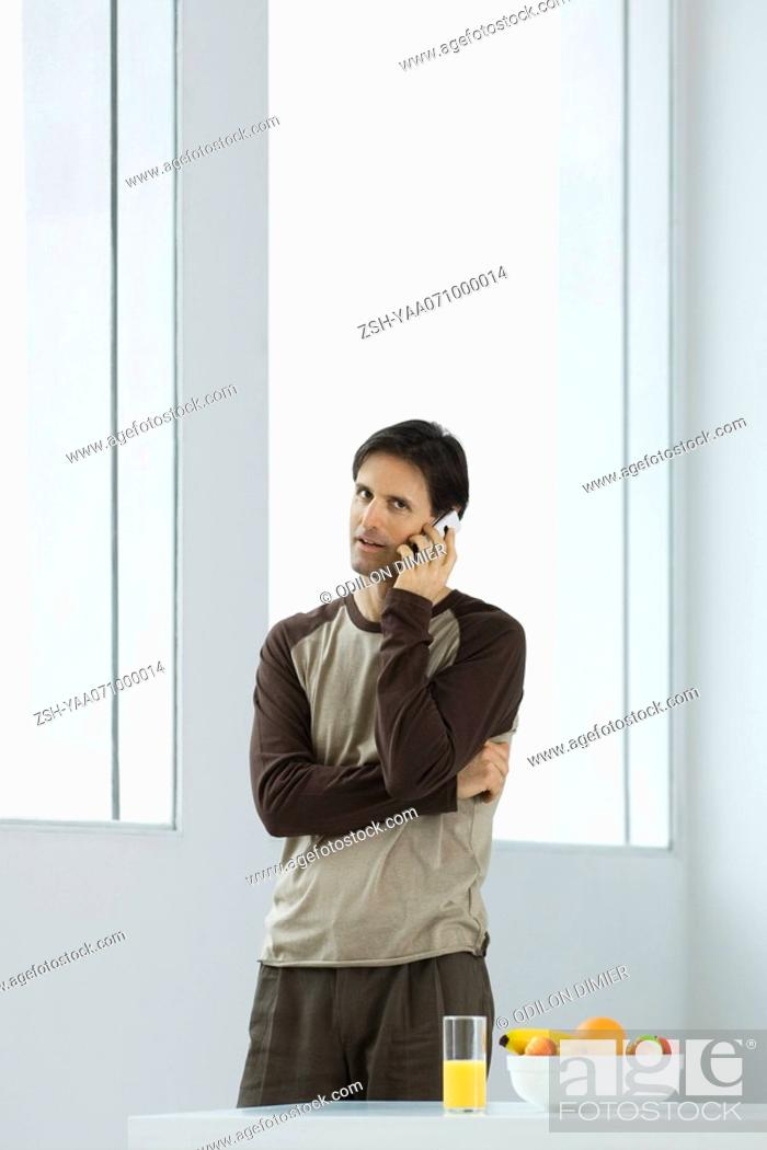 Stock Photo: Man talking on cell phone, looking at camera, juice and fruit bowl on table.